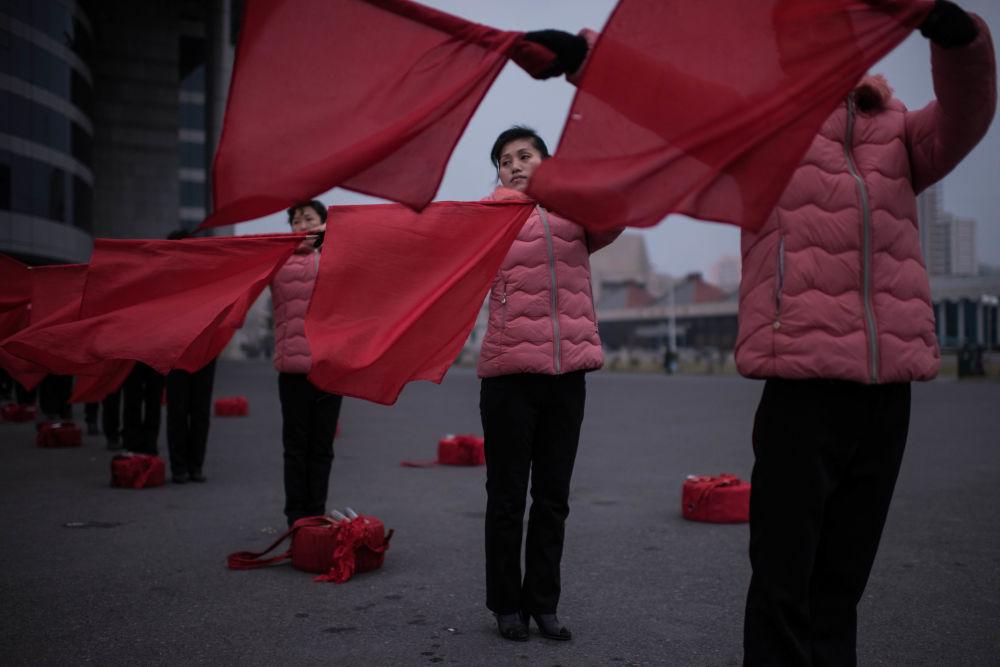 Przedstawienie z flagami na ulicy Pjongjangu