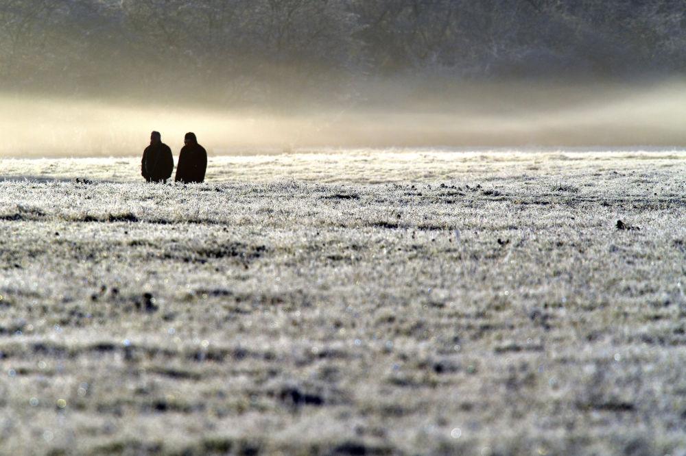 Ludzie spacerują po zamarzniętym polu