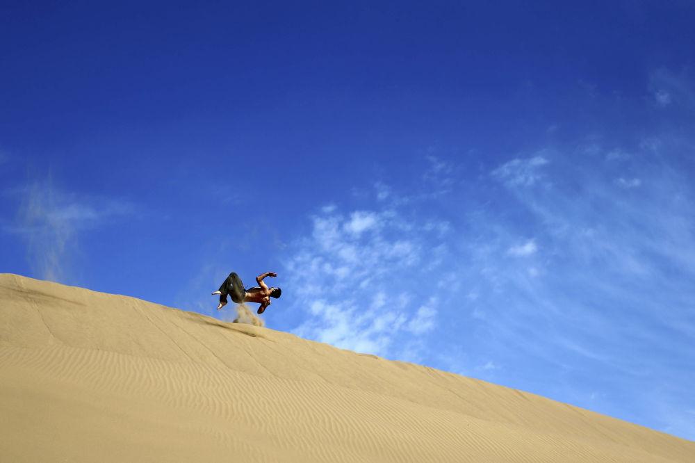 Mężczyzna robi salto na pustyni Mesr w Iranie