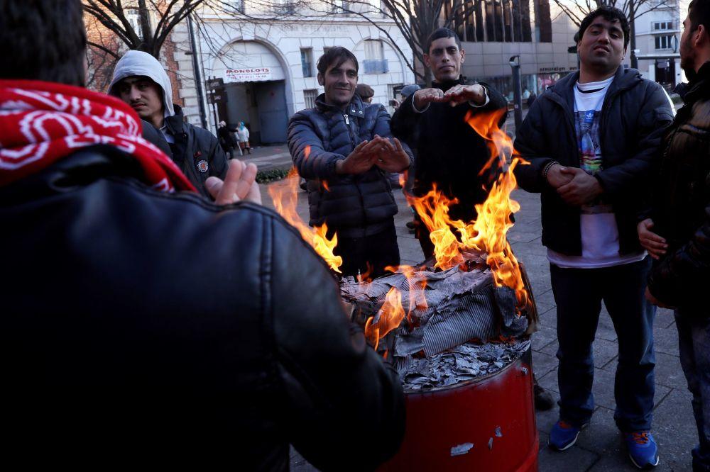 Mężczyźni grzeją się przy ognisku w obozie dla uchodźców w Saint-Denis w Paryżu
