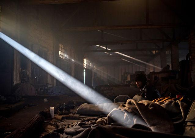 Uchodźca odpoczywa w prowizorycznym schronie w opuszczonym magazynie w Belgradzie