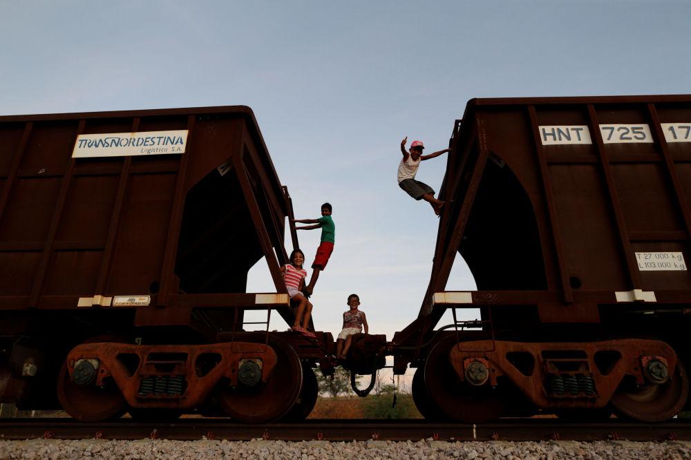 Dzieci bawią się na pociągu towarowym niedaleko niedokończonej kolei Transnordestina do przejazdu wagonów towarowych