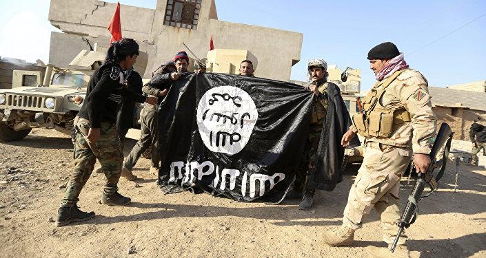 Iraccy wojskowi świętują odbicie wioski pod Mosulem z rąk PI, trzymając flagę pokonanych terrorystów