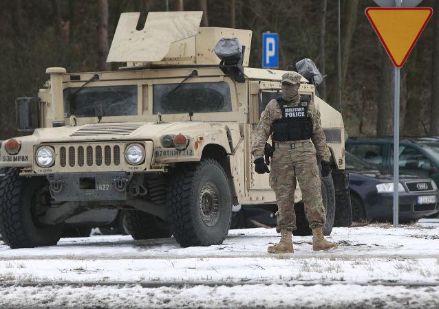 Amerykański wojskowy stoi obok pojazdu opancerzonego w Polsce