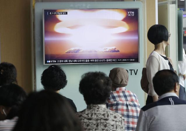 Ludzie oglądają w telewizji wiadomości o testach jądrowych w Korei Północnej
