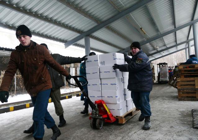 Pracownicy MSN DRL rozładowują ciężarówkę MNS Rosji z pomocą humanitarną dla mieszkańców Donbasu w Doniecku