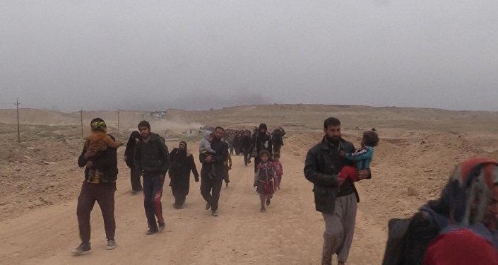 Rodziny z dziećmi pieszo opuszczają Mosul, aby wsiąść do autobusów do Erbilu