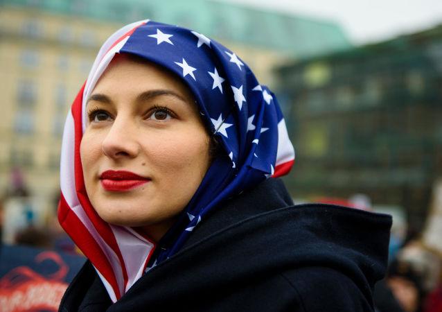 Kobieta w hidżabie z flagi USA podczas protestów w Berlinie.