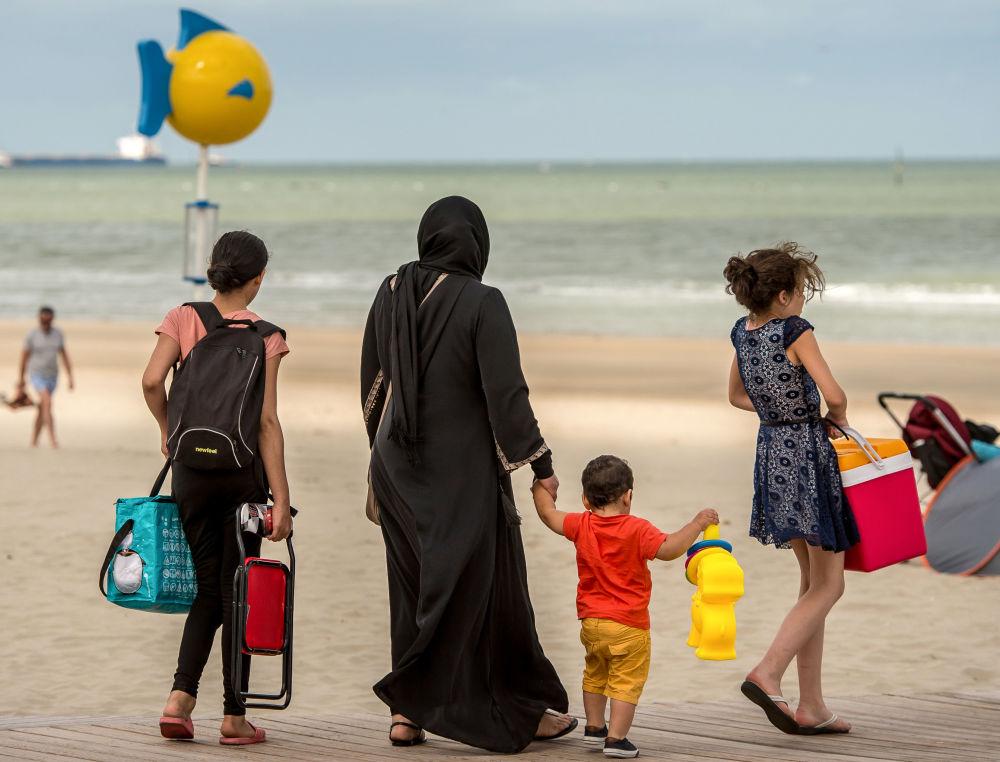 Muzułmanka w hidżabie z dziećmi na plaży na północy Francji.