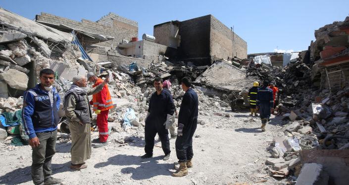 Iraccy cywile i ratownicy na gruzach po nalotach na Mosul