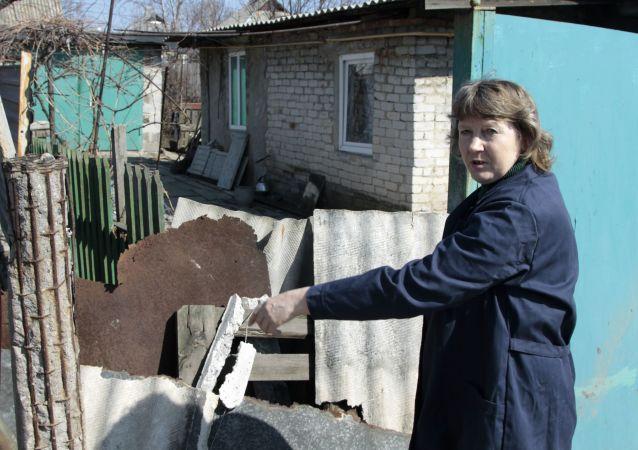 Mieszkańka Doniecka pokazuje skutki ostrzału swojego domu