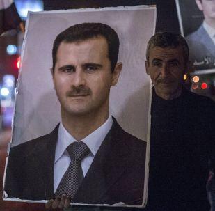Mieszkańcy Damaszku trzymają w rękach portret syryjskiego prezydenta Baszara Asada