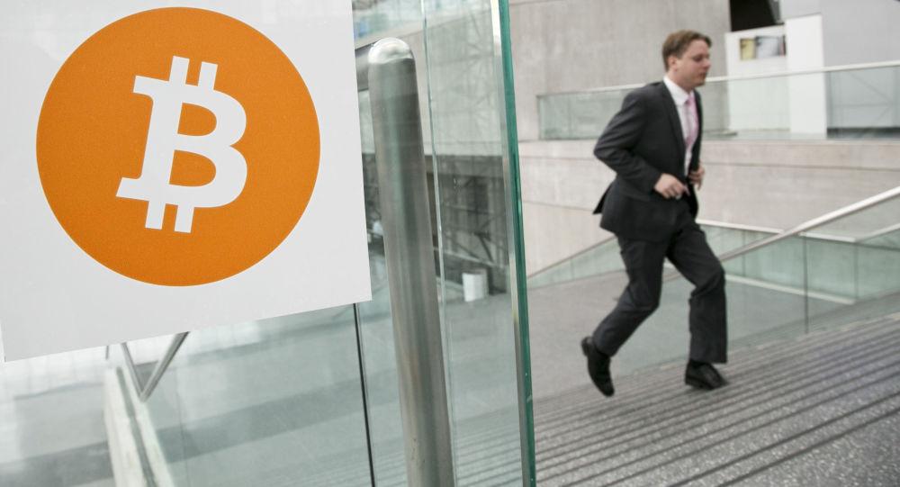 Mężczyzna mijający logotyp Bitcoin