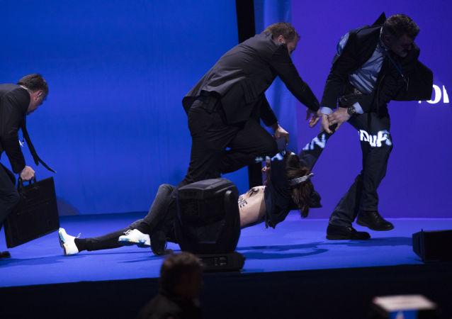 Ochroniarze wyprowadzają ze sceny aktywistki Femen, które próbowały zerwać wystąpienie Marine Le Pen