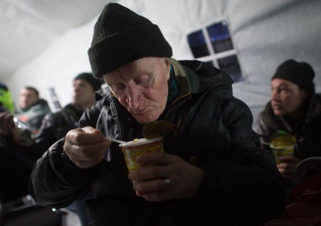 Mężczyzna je obiad w punkcie dla bezdomnych