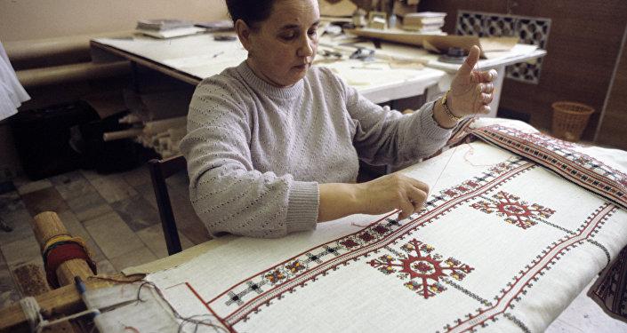 """Kobieta, wyszywająca tradycyjny czuwaski wzór w firmie rzemiosła artystycznego """"Paha tere"""