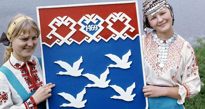 Uczennice w narodowych czuwaskich strojach trzymają herb miasta Czeboksary - stolicy Czuwaszji