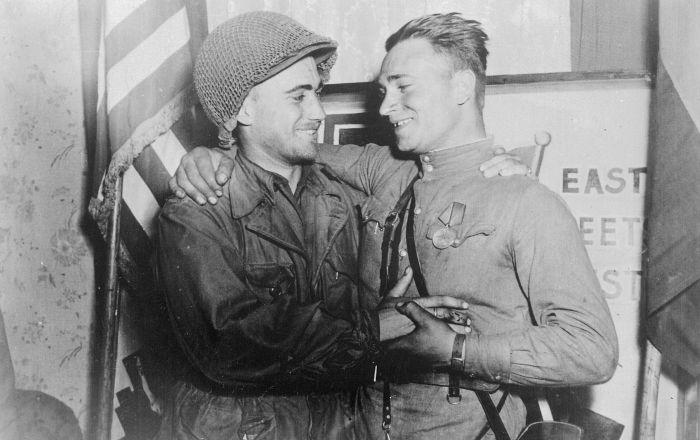 Podporucznik William Robertson z US Army oraz porucznik Aleksander Sylwaszko z Armii Czerwonej cieszący się ze spotkania się nawzajem, stojący naprzeciw napisu East Meets West, podczas spotkania armii amerykańskiej z armią radziecką w pobliżu Torgau, 27 kwietnia 1945 roku