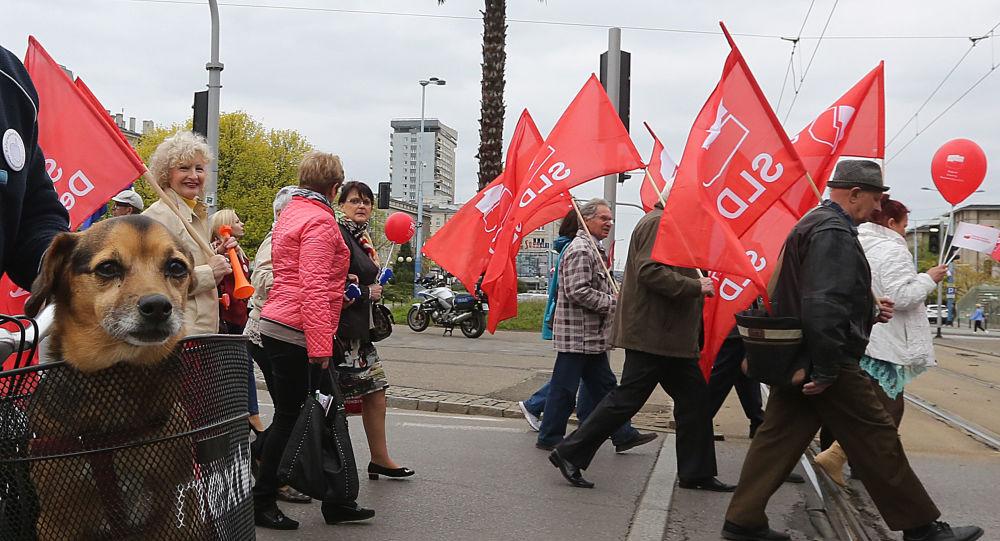 Uczestnicy marszu z okazji 1 maja z flagami SLD