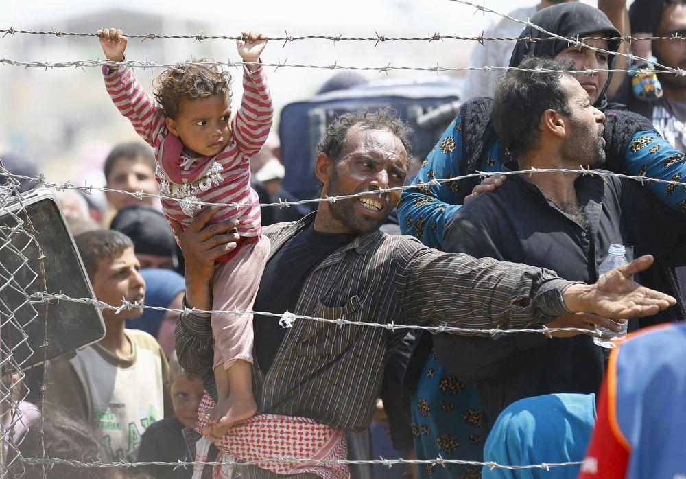 Syryjski uchodźca z córką na rękach na granicy z Turcją