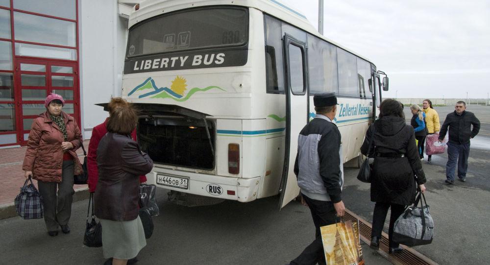 Pasażerowi wychodzący z autobusu w celu przejścia kontroli celnej na punkcie granicznym Szebekino