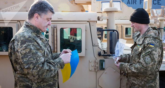 Prezydent Ukrainy Petro Poroszenko podczas powitania samolotu Sił Powietrznych USA z amerykańskimi transporterami opancerzonymi