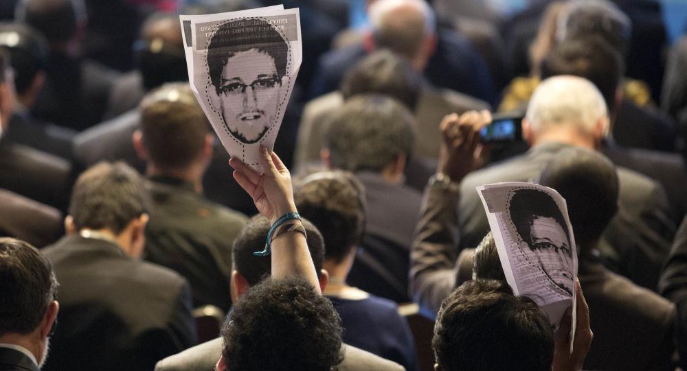 Portret Edwarda Snowdena w rękach uczestników konferencji nt. rozwoju internetu. Brazylia