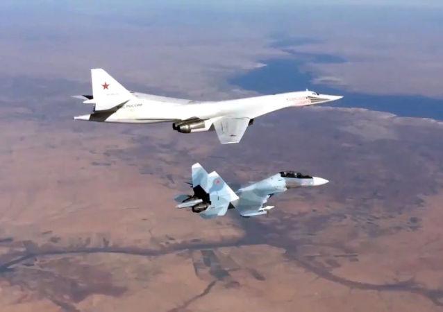 Myśliwiec Su-30SM i bombowiec Tu-160 Sił Powietrzno-Kosmicznych Rosji, który wystrzeliwuje pociski manewrujące nad Morzem Śródziemnym na obiekty PI w Syrii