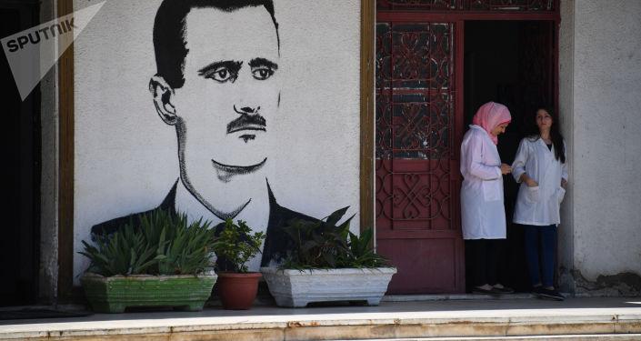 Graffiti przed wejściem do zakładu mleczarskiego w Homs