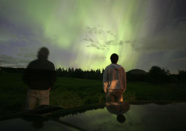 Ludzie obserwują zorzę polarną w Szwecji