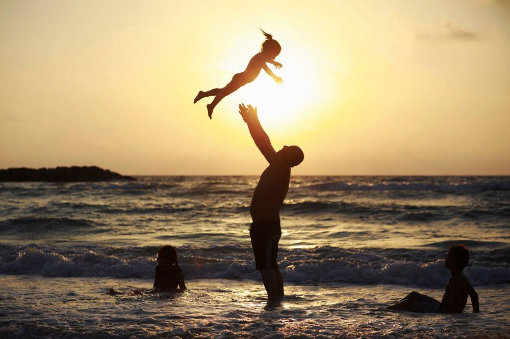 Mężczyzna bawi się z córką na plaży podczas świętowania Uraza-Bajramu w Aszkelonu, Izrael