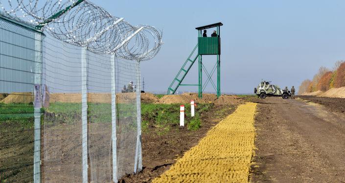Ukraińscy funkcjonariusze straży granicznej obok ogrodzenia na granicy Rosji i Ukrainy