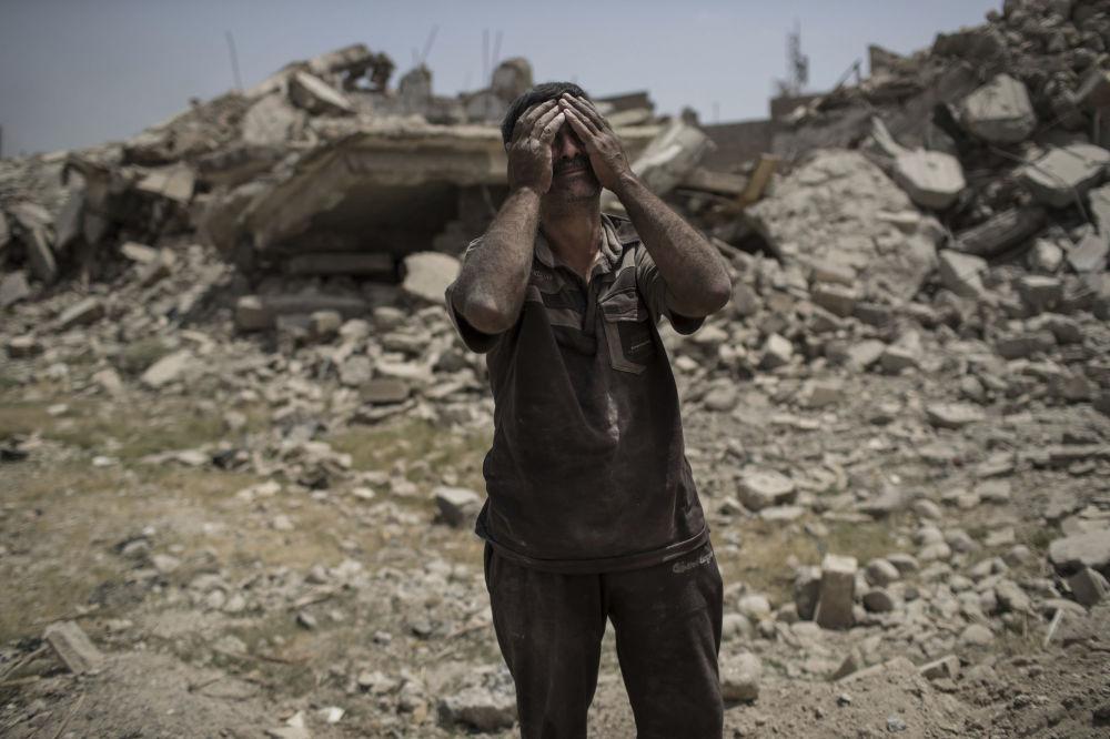 Mieszkaniec Mosulu rozpacza, widząc ciało swojej zmarłej córki...