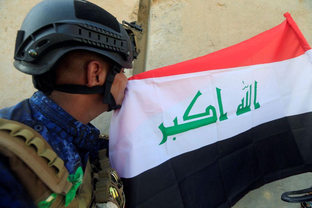 Pracownik federalnej policji Iraku całuje iracką flagę w zachodnim Mosulu