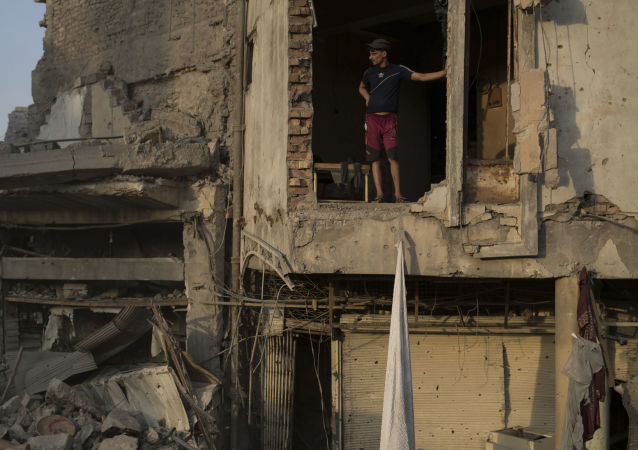 Oficer federalnej policji Iraku stoi w zniszczonym budynku w Mosulu