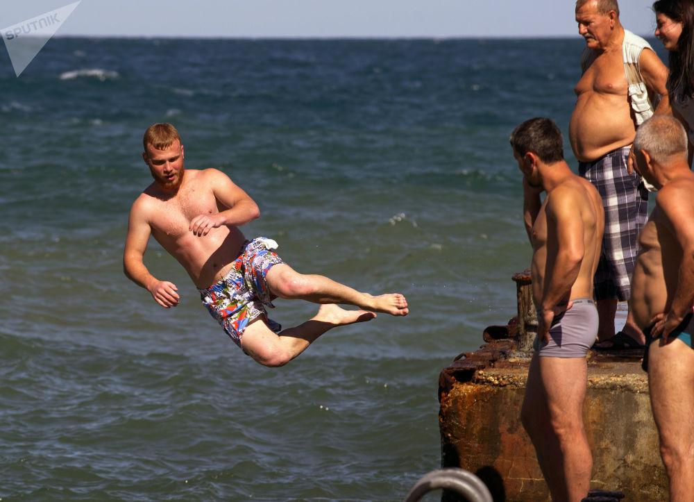 Urlopowicze skaczą z molo w miejscowości Partenit na Krymie.