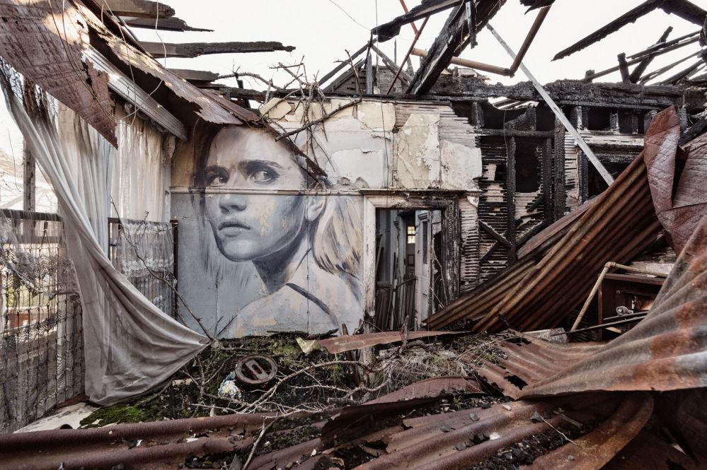 Portret kobiety australijskiego ulicznego artysty pracującego pod pseudonimem Rone na ścianie opuszczonego budynku