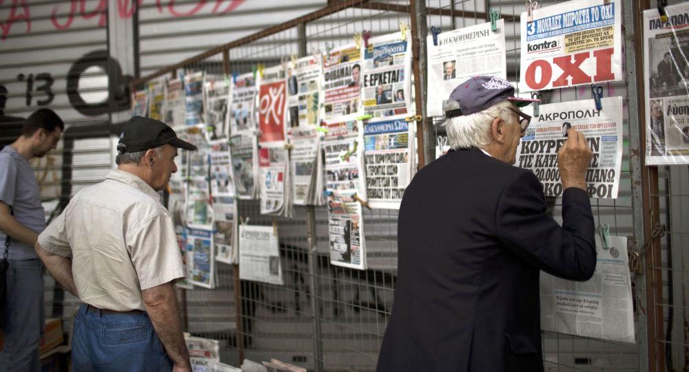 Mieszkańcy Aten czytają najnowsze gazety wystawione w centrum miasta