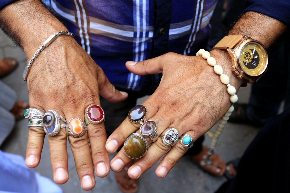 Sprzedawca prezentuje srebrne pierścienie na targu w Bagdadzie, Irak