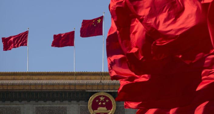 Chińskie flagi nad budynkiem Wielkiej Hali Ludowej w Pekinie