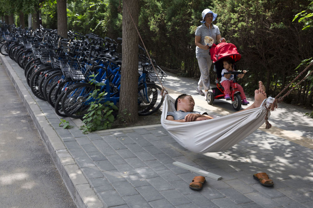 Mężczyzna śpi w hamaku na jednej z ulic w Pekinie