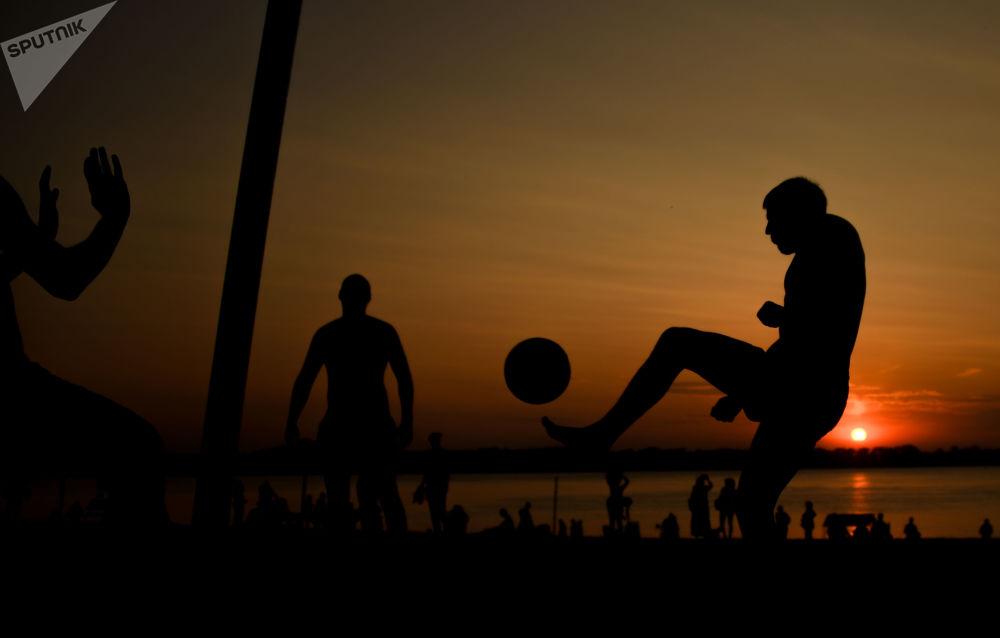 Odpoczywający ludzie grają w piłkę nożną na plaży nad brzegiem Wołgi w Samarze.