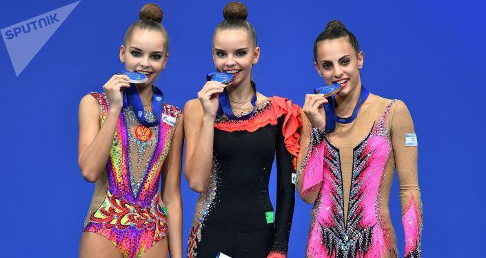 Gimnastyczki Arina Awerina, Dina Awerina i Lina Aszram podczas ceremonii rozdania nagród w mistrzostwach świata w gimnastyce w Pesaro.