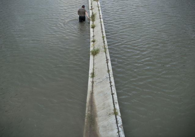 Kierowca sprawdza głębokość zalania na drodze w wyniku huraganu Harvey w stanie Teksas w USA