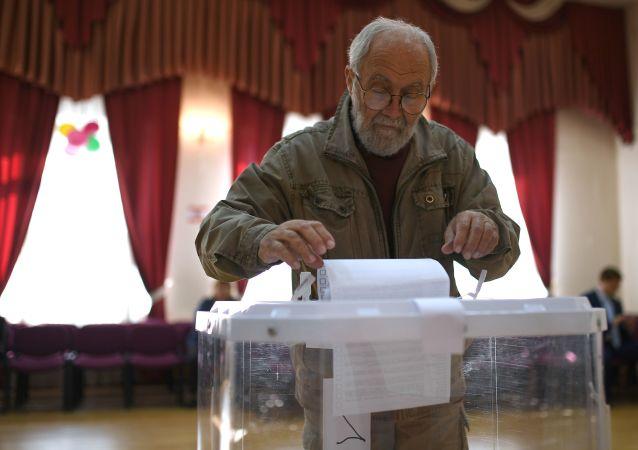 Wyborca w lokalu wyborczym w Moskwie