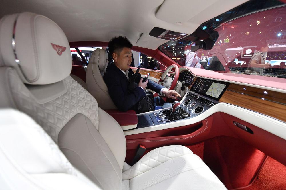 Mężczyzna za kierownicą samochodu Bentley podczas Międzynarodowego Salonu Motoryzacyjnego we Frankfurcie