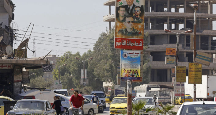 Plakat z wizerunkiem prezydenta Syrii Baszara Asada i jego rodziny na ulicy Damaszku