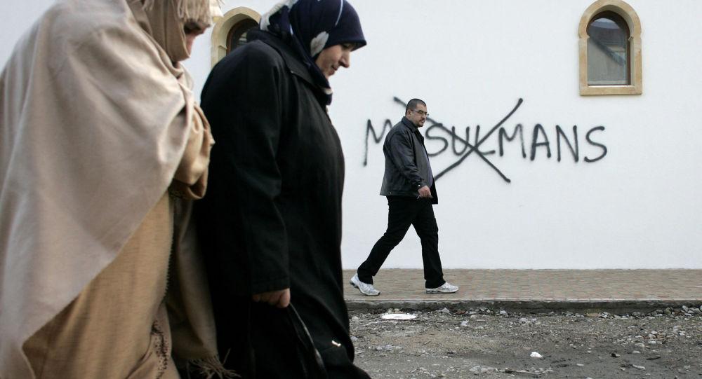 Muzułmanie idący obok ściany z obelgami
