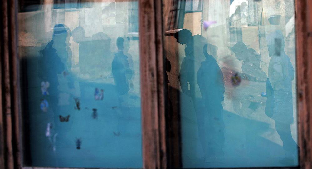 Dzieci odbijają się w oknie szkoły w Kosowo