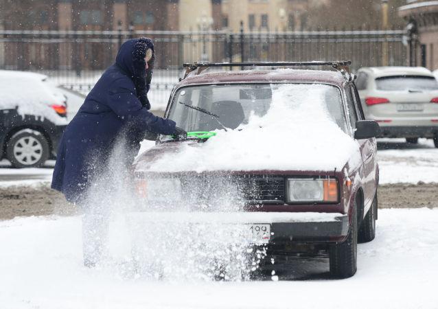 Kobieta czyści samochód ze śniegu